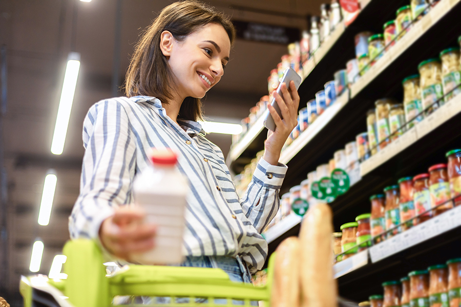 Female customer holding smartphone standing in store taking products